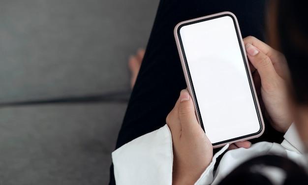 Vue rapprochée des mains de femme tenant un smartphone à écran blanc avec espace de copie.