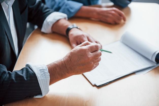 Vue rapprochée des mains d'un homme d'affaires senior avec un stylo lors de la réunion de la conférence.