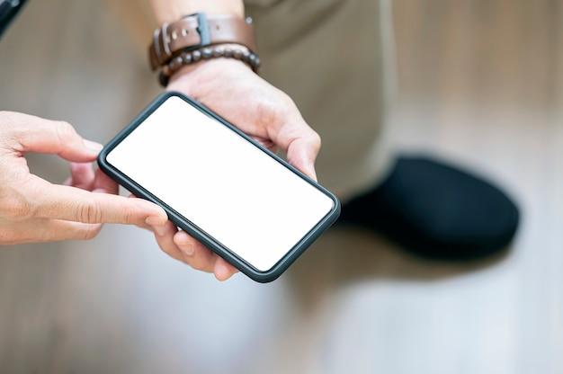 Vue rapprochée des mains de l'homme tenant un smartphone à écran blanc.