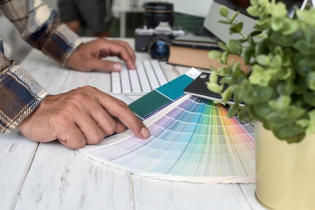 Vue rapprochée des mains de jeune femme designer travaillant avec la palette de couleurs au bureau.