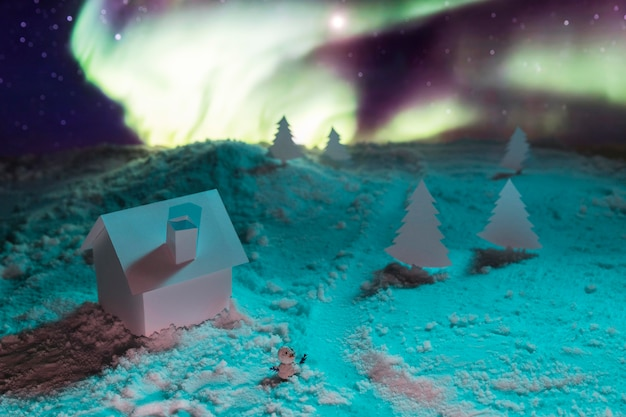 Vue rapprochée de la maison sur la neige avec des aurores boréales