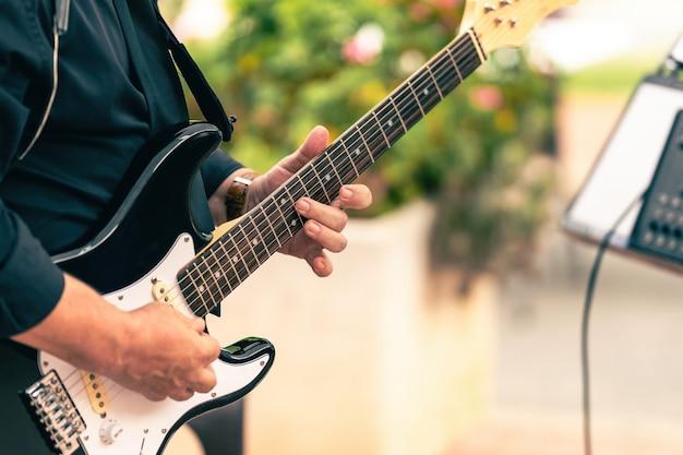 Vue rapprochée d'un musicien jouant de la guitare électrique lors d'un concert en direct à l'extérieur