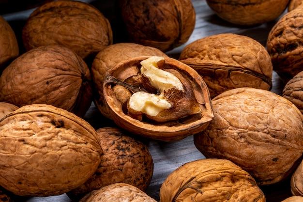 Vue rapprochée de noix fermées et cassées éparpillées sur un bois