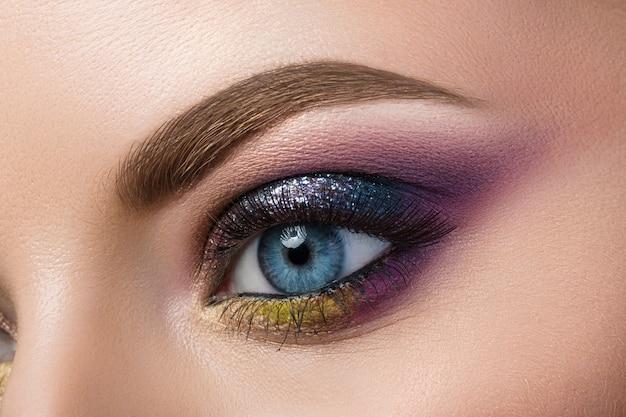 Vue rapprochée de l'oeil féminin bleu avec un beau maquillage créatif moderne