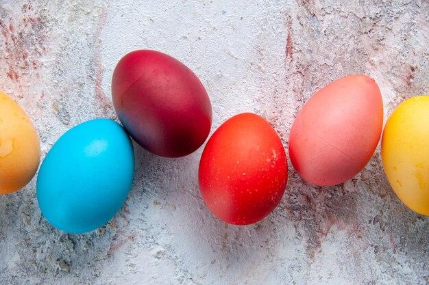 Vue rapprochée d'œufs colorés déposés côte à côte sur la surface de la glace