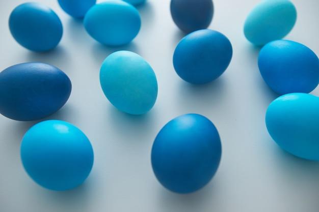 Vue rapprochée d'oeufs de pâques bleus peints à la main disposés en composition minimale sur fond blanc, espace copie