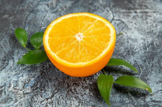 Vue rapprochée de l'orange fraîche coupée en deux avec des feuilles sur fond gris photo stock