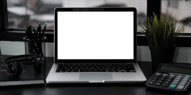 Vue rapprochée d'un ordinateur portable à écran blanc ouvert avec des fournitures de bureau dans un bureau moderne