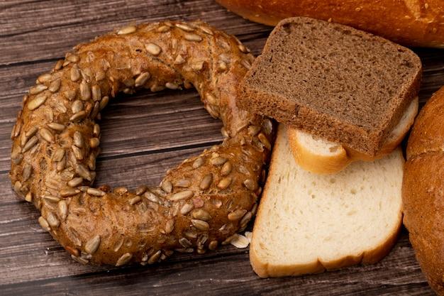 Vue rapprochée de pains en tranches de seigle et de pains blancs bagel sur fond de bois
