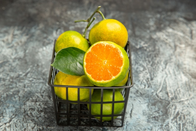 Vue rapprochée d'un panier plein de mandarines vertes fraîches et coupées en deux mandarines sur fond gris