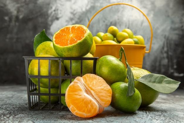 Vue rapprochée d'un panier et d'un seau plein de mandarines vertes fraîches coupées en deux et de mandarines pelées sur fond gris