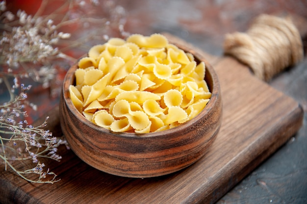 Vue rapprochée de pâtes non cuites dans un bol brun sur une planche à découper en bois sur table de couleurs mixtes