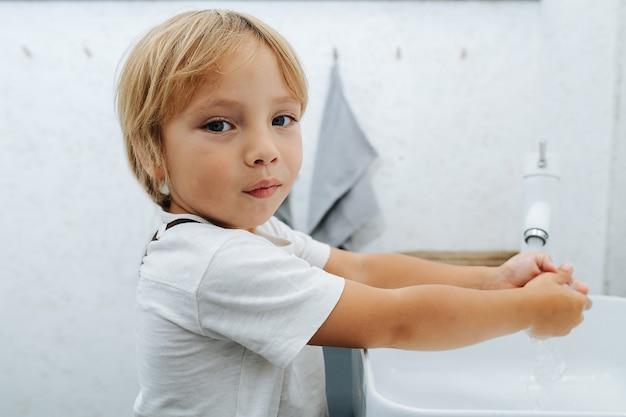 Vue rapprochée d'un petit garçon se lavant les mains dans le lavabo de la salle de bain