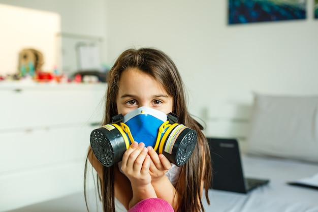 Vue rapprochée d'une petite fille dans un grand masque de protection contre les virus covid-19 et la poussière dans l'air.