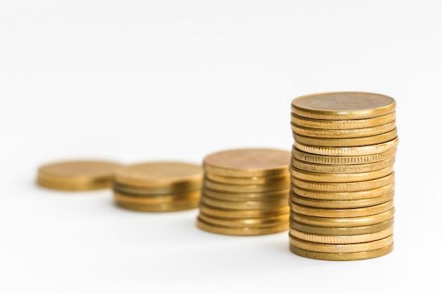 Vue rapprochée des pièces de monnaie de 5 roupies indiennes empilées sur fond blanc.