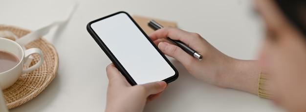 Vue rapprochée de pigiste à l'aide d'une maquette de smartphone pour contacter le client