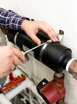 Vue rapprochée de la pince de vissage plombier reliant deux tuyaux