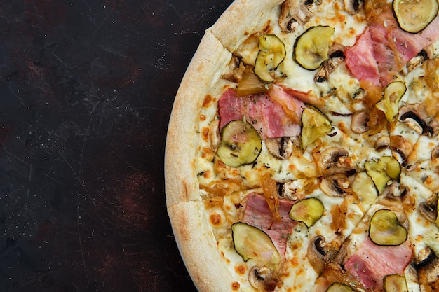 Vue rapprochée de la pizza au bacon, aux champignons, au concombre mariné et à l'oignon caramélisé