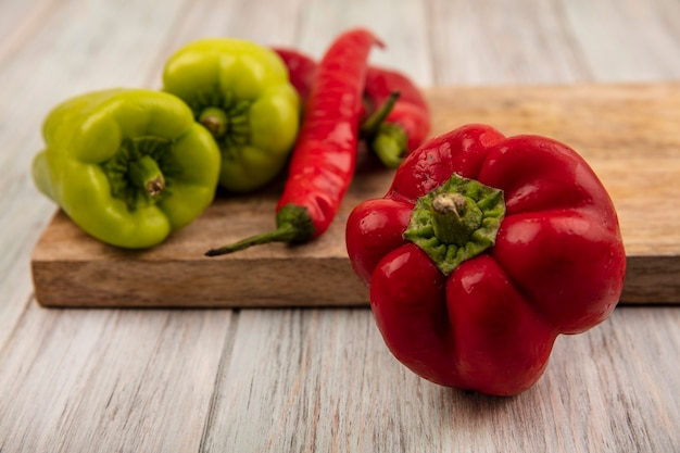 Vue rapprochée d'un poivron rouge frais avec bell et piments colorés sur une planche de cuisine en bois sur un fond en bois gris