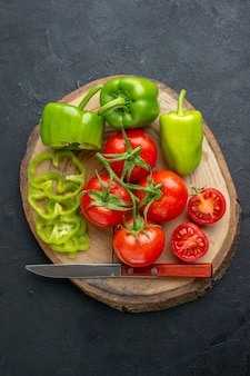 Vue rapprochée de poivrons verts hachés entiers et de tomates fraîches sur une planche à découper en bois sur une surface noire