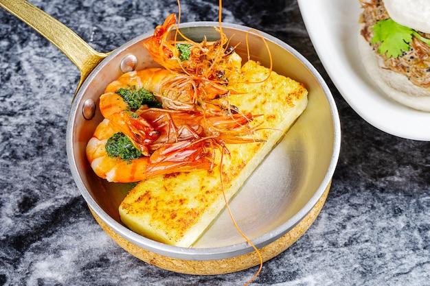 Vue rapprochée sur la polenta grillée traditionnelle avec de grosses crevettes