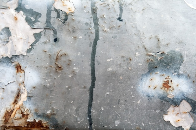 Vue rapprochée de la porte métallique d'une vieille voiture avec des traînées de peinture, de l'écaillage et de la rouille