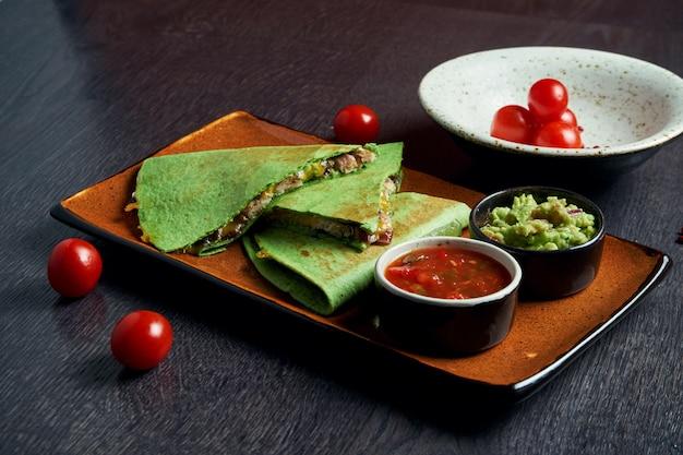 Vue rapprochée quesadilla de tortilla verte au poulet, fromage sur une plaque brune avec sauce rouge sur une surface en bois. cuisine traditionnelle mexicaine