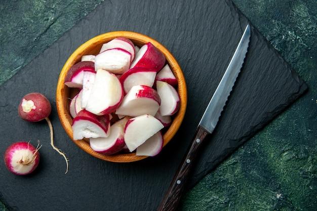 Vue rapprochée de radis frais entiers et hachés dans un bol et un couteau sur une planche à découper de couleur foncée sur fond de couleurs mélangées noir vert avec espace libre
