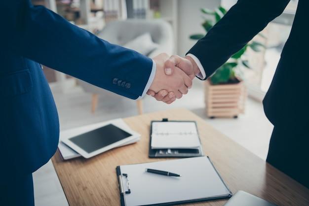 Vue rapprochée recadrée de deux mains masculines secouant sur un bureau de table signé service d'assurance-vie de voiture d'affectation de contact d'entreprise dans un poste de travail intérieur blanc clair à l'intérieur