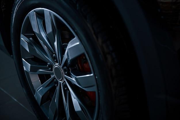 Vue rapprochée de la roue de la voiture automobile garée à l'intérieur.