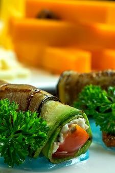 Vue rapprochée des rouleaux d'aubergine frits avec du fromage à la crème à l'ail et de la tomate