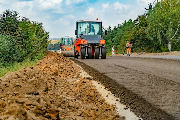 Vue rapprochée sur les rouleaux de la route travaillant sur le nouveau chantier de construction de la route
