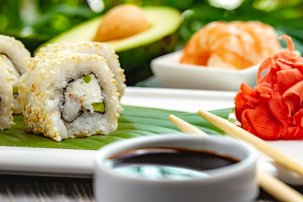 Vue rapprochée de rouleaux de sushi avec du riz, des crevettes, de l'avocat et du fromage à la crème avec de la sauce de soja sur des feuilles de bambou