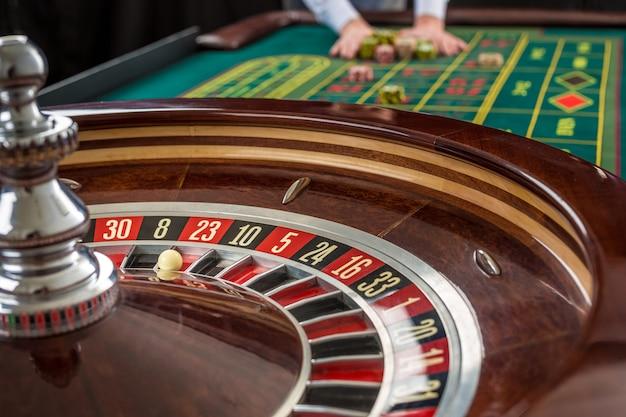 Vue rapprochée de la roulette et des tas de jetons de jeu sur une table verte au casino. l'homme remet des jetons de casino sur la table de roulette