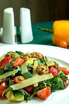 Vue rapprochée de la salade fraîche au parmesan, avocat, noix, tomates cerises et fraises dans un bol blanc