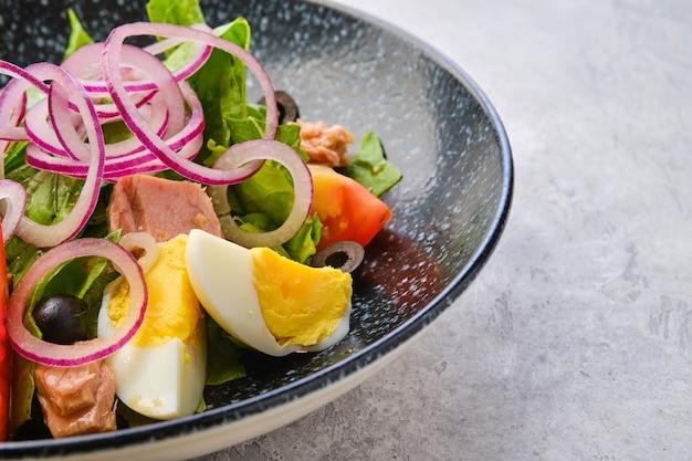 Vue rapprochée de la salade avec laitue, saumon, tomate, œuf à la coque et oignon aux olives