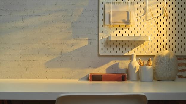 Vue rapprochée de la salle de bureau à domicile avec espace copie, livre, papeterie et décoration sur table près de la fenêtre