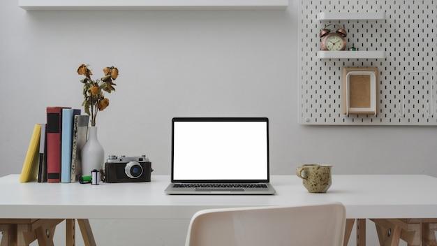 Vue rapprochée de la salle de bureau avec ordinateur portable à écran blanc, fournitures de bureau, appareil photo, tasse à café et décorations sur bois blanc