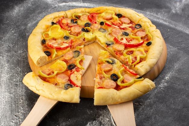 Vue rapprochée de la savoureuse pizza au fromage avec tomates rouges, olives noires, poivrons et saucisses sur le bureau sombre