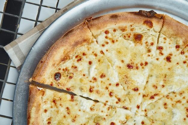 Vue rapprochée sur une savoureuse pizza italienne aux quatre fromages faits maison dans une composition avec des épices et des tomates cerises sur un tableau blanc. vue de dessus. mise à plat de nourriture