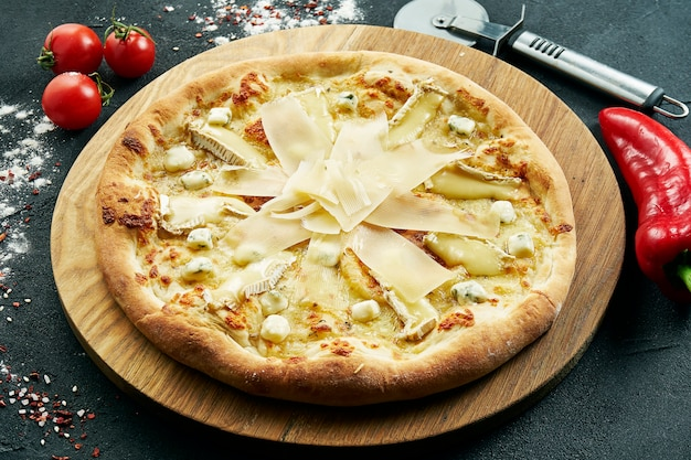Vue rapprochée sur la savoureuse pizza italienne aux quatre fromages maison sur une planche de bois dans une composition avec des épices et des tomates cerises sur un tableau noir