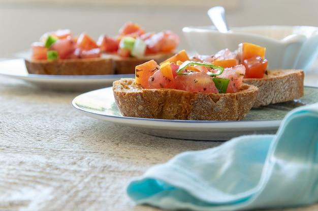 Vue rapprochée de savoureux apéritifs italiens à la tomate - bruschetta, sur des tranches de baguette grillée