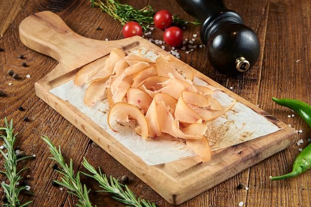 Vue rapprochée sur de savoureux basturma de poulet en tranches sur parchemin sur une planche de bois sur une surface en bois dans une composition avec des épices. collation de bière. pastä ± rma