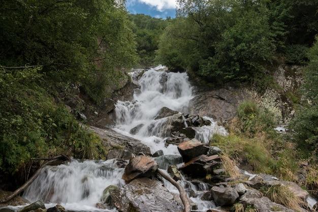 Vue rapprochée de la scène de la cascade dans les montagnes, parc national de dombay, caucase, russie. paysage d'été, temps ensoleillé et journée ensoleillée
