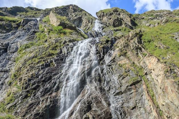Vue rapprochée des scènes de cascade dans les montagnes, parc national dombai, caucase, russie, europe. paysage d'été, temps ensoleillé, ciel bleu dramatique et journée ensoleillée