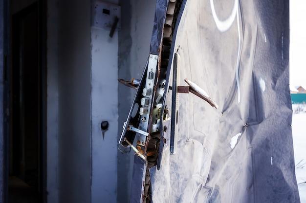 Vue rapprochée de la serrure cassée et du cadre de porte endommagé