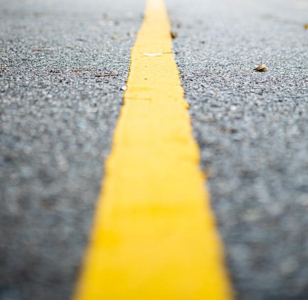 Vue rapprochée d'une seule ligne jaune sur la route en flou artistique, vue en perspective à un point.