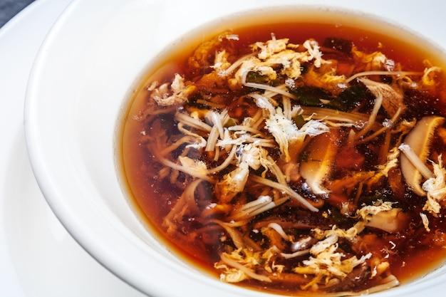 Vue rapprochée sur la soupe de crabe frais aux champignons shiitake servi dans un bol blanc