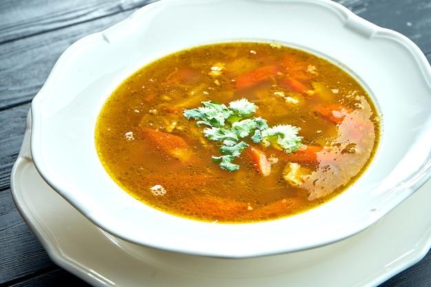 Vue rapprochée de la soupe ou du ragoût de chorba avec du bœuf, des herbes et du piment dans un bol blanc sur une surface en bois, cuisine turque traditionnelle