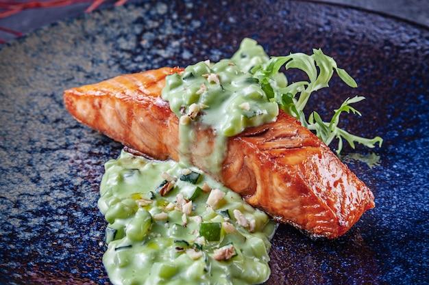 Vue rapprochée sur le steak de saumon grillé avec sauce verte sur plaque sombre. porno alimentaire. copiez l'espace pour la conception. fond de nourriture de restaurant. poissons de fruits de mer pour le menu.